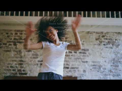 Handheld of joyful african american teeanger girl have fun dancing near bed at home