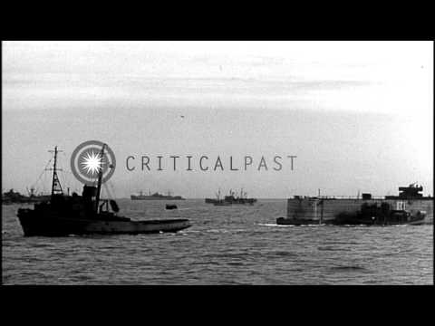 Warships and concrete barge with anti-aircraft guns towed by tugs, head towards t...HD Stock Footage