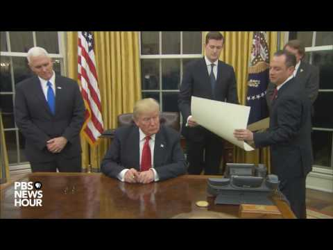 Watch President Trump's first signings in Oval...