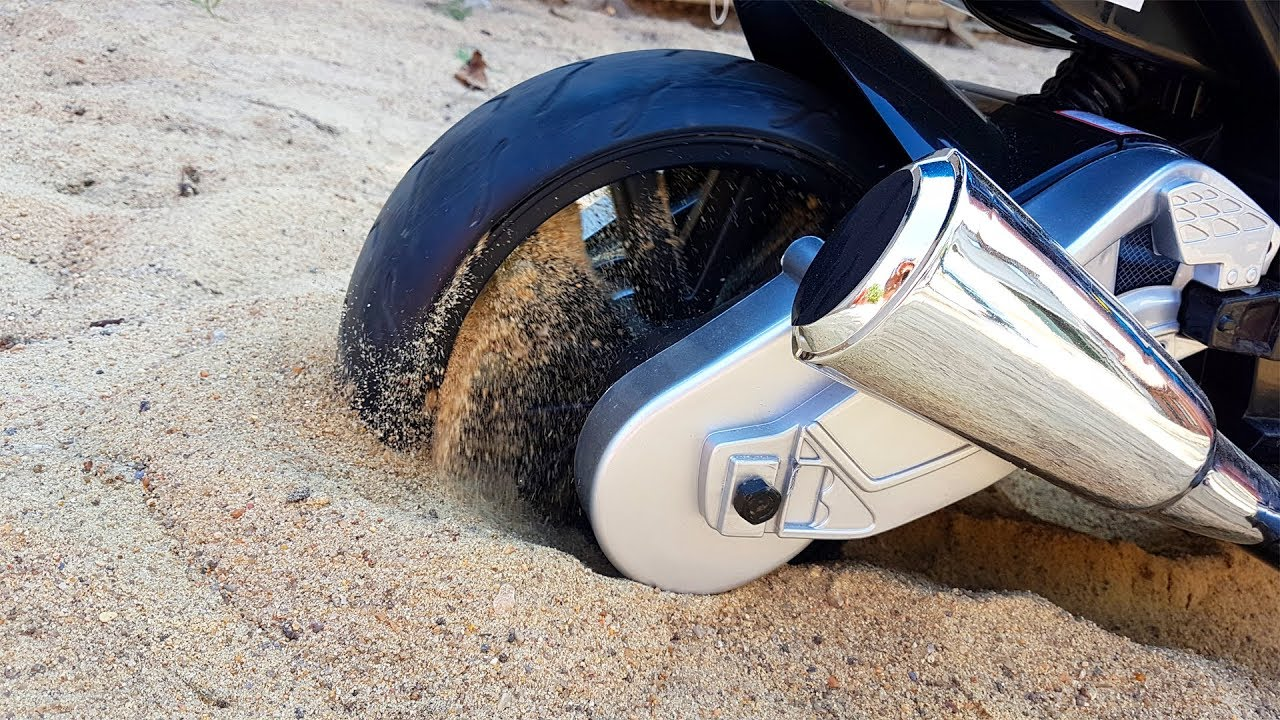 The power wheels sport bike stuck in the sand