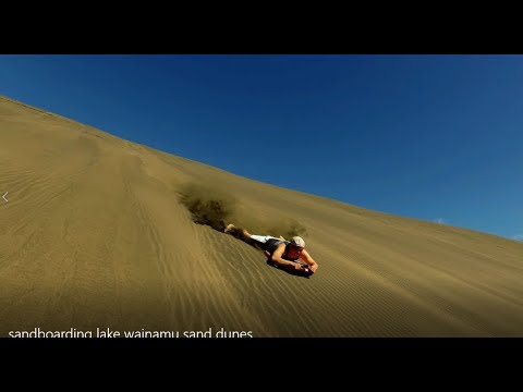 Sandboarding in Lake Wainamu Sand Dunes Auckland New Zealand
