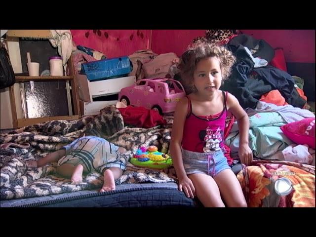 Mãe de duas crianças se prepara para deixar casa em área de risco