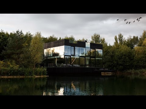 Mecanoo builds glass house partly submerged in a lake in the English countryside