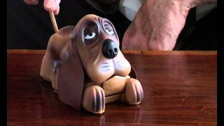 A novelty money bank. Push the dog's tail and he sticks his tongue ...