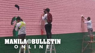 Freelance artists join together to paint a massive mural along Buendia
