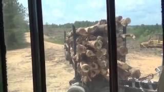 Unloading log trucks with a John Deere track loader