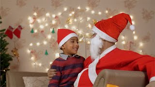 A little boy sits on Santa's lap gets a christmas gift