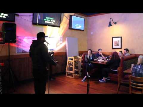 Karaoke singer singing I Will Always Love You by Whitney Houston