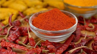 Powdered red chili (laal mirch) and turmeric (haldi) kept in the bowl along with Indian Spices - turmeric roots and dried red chilies