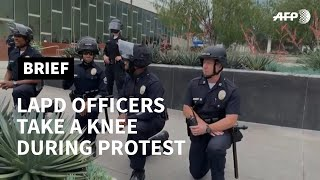 Los Angeles officers take a knee during George Floyd protest | AFP Los Angeles police officers take a knee in solidarity with protesters who are demonstrating following the killing of African American George Floyd who died after ..., From YouTubeVideos