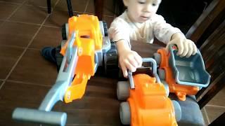 ► Мальчик играет оранжевым экскаватором и игрушечной машинкой дома на диване.