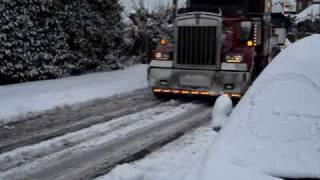 big rig truck pulls 18 wheeler uphill in snow