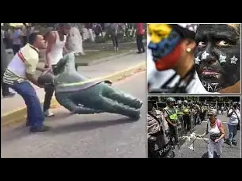 Men are seen destroying Hugo Chávez statue during protest