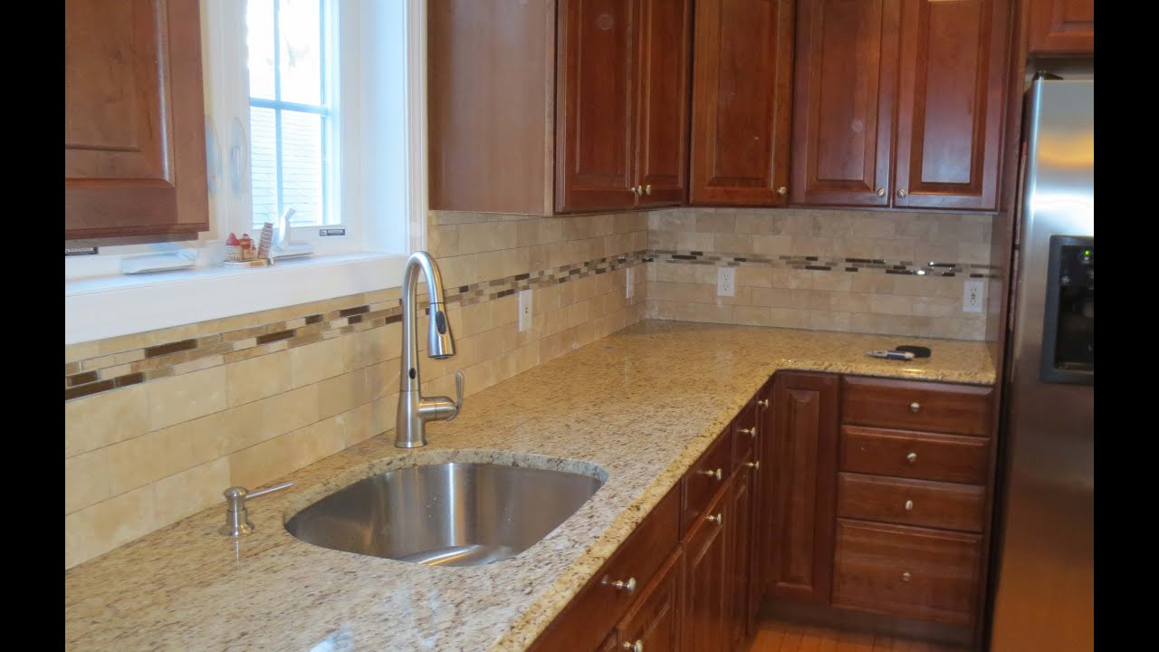 Travertine subway tile kitchen backsplash with a mosaic glass tile