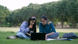 Two young girls studying and working on a laptop together in their college park