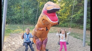 Dominika and Rinat playing in the playground with toy Dinosaur