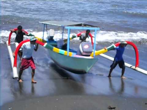 balinese fisherman carry boat up sea wall
