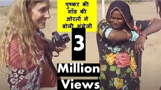 foreign tourist photographing rajasthani village women kids in pushkar camel fair rajasthan