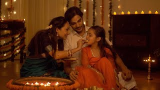 South Indian family dressed in traditional wear is celebrating Diwali at home - Happy Family