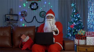 Busy old Santa working on his laptop at home during Christmas time in India