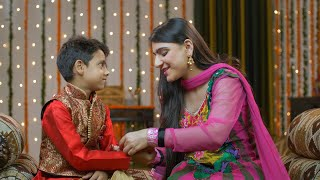 Beautiful elder sister tying rakhi on her younger brother's wrist celebrating Raksha Bandhan