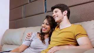 Young happy couple sitting on couch and watching television and discussing