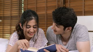 Young happy couple reading book together in bedroom