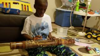 omar having fun with a malagasy musical intrument, antananarivo