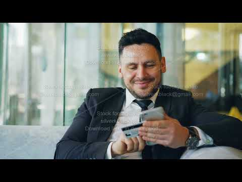 Smiling Caucasian businessman in suit using online banking holding credit card and smartphone in his