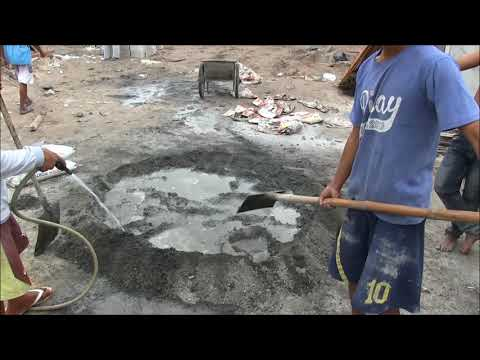 FILIPINO WORKERS PUTTING SAND IN BAGS MIXING CEMENT IN THE PHILIPPINES