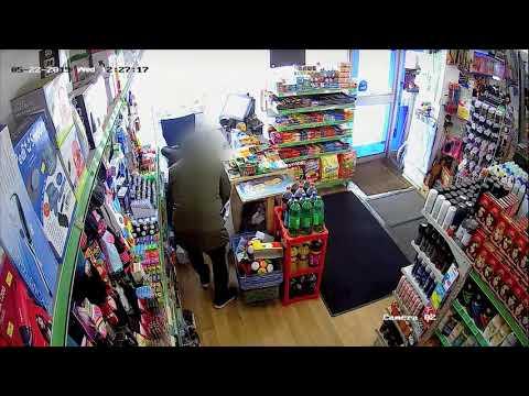 CCTV shows robber threaten shopkeeper with suspected gun in Manchester