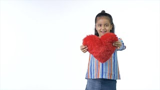 The young girl happily showing her new heart-shaped toy isolated over white background