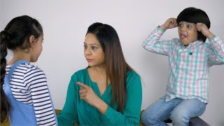 Angry Indian woman scolding her little daughter while her son teases her from behind
