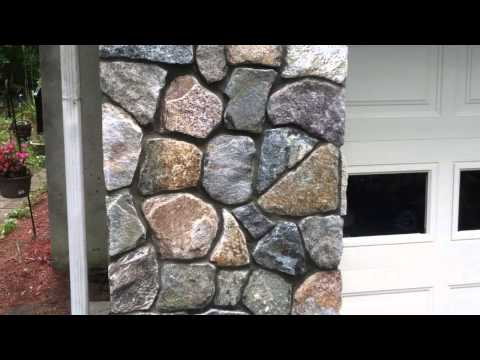 Stone Veneer installation on a poured concrete foundation and retaining wall.