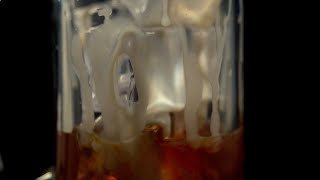 Closeup shot of milk being poured into coffee with ice cubes