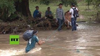 Migrantes hondureños intentan cruzar el río en la frontera con El Salvador