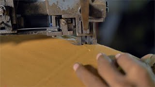 Closeup shot of carton being stapled with machine in cardboard factory