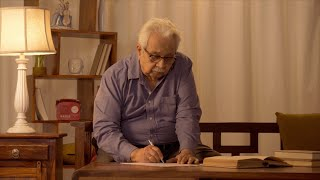 An old Indian man wearing a blue shirt writing notes at home