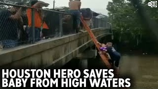 Man carries baby up ladder, out of high water to safety