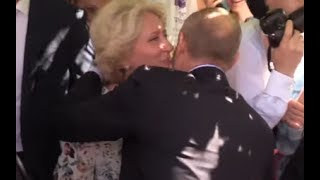 PUTIN SPEAKS ENGLISH: A lucky woman gives a kiss on the cheek to Putin in the centre of Moscow