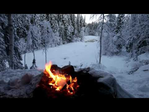 Crackling fire in the snow overlooking a frozen river in deep winter