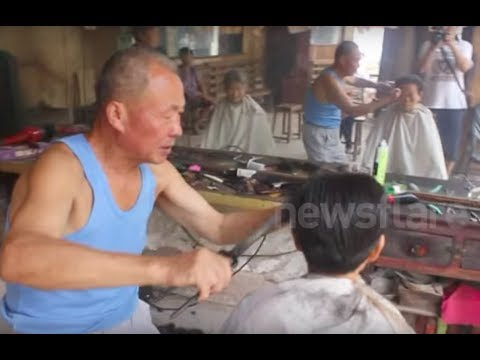 Chinese barber practising the rare art of cutting hair with hot tongs
