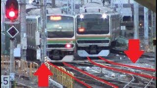 すれ違う列車がポイント分岐通過で接触しそうに見える早朝の東京駅新幹線ホームから見た東海道本線E231系の発着