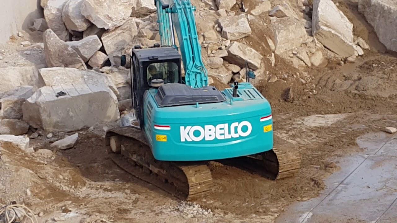 Kobelco 220 XD Excavator in granite quarry removing big granite block