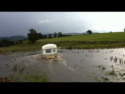 pulling caravan through flooded field.