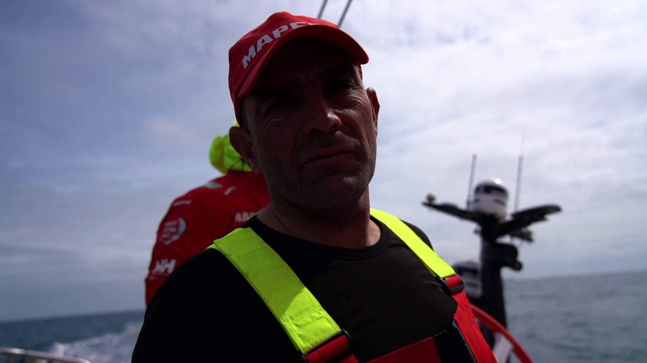 Xabi, in the cockpit, trims the main and talks in Spanish about tactical situation. Repeats in English: 70 miles to go, very complicated really. Yesterday we were going east down the Danish coast with Dongfeng, but the last weather forecast changed a little, and we decided that the westerly option was better. Unfotunately they are in front of us, and Akzo. Still a good downwind of 30 miles today, but we will keep fighting and see what happens. Brunel and AkzoNobel ahead of them. Joan at the nav station. Blair on the helm. Willy, Sophie, Blair and Neti on the bow. Xabi: Main on. Hold. Blair's salty hands. Two boats closer in front of them.