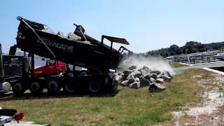 Dump trucks unloading big rocks