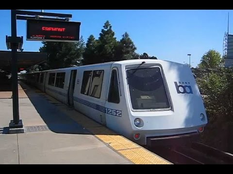 USA: Richmond, BART train in platform and Union Pacific freight train passing