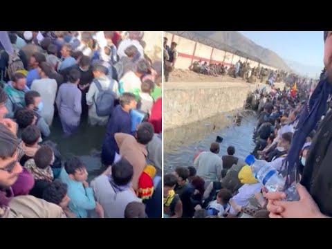 Afghans wait in knee-deep water outside Kabul airport in desperate bid for evacuation