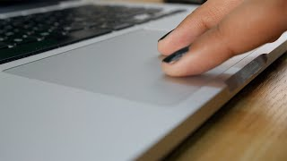 Close up of a girl moving her fingers on a touchpad while surfing on her laptop
